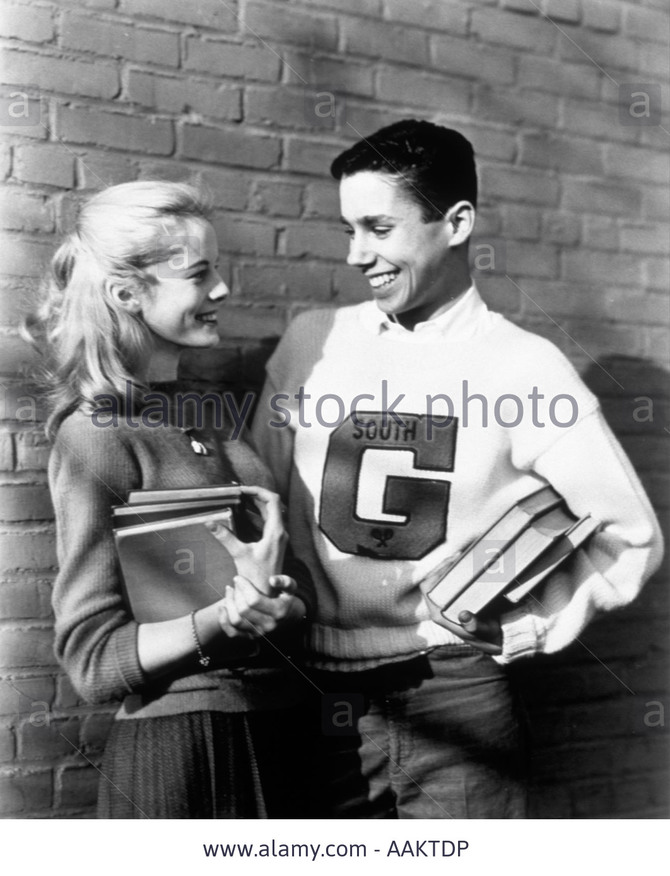 1950s-teenage-couple-holding-books-and-smiling-leaning-against-wall-AAKTDP.jpg